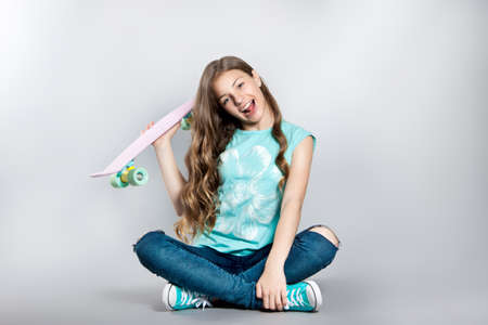 Girl posing with skateboard sitting in the studio. Joy, smile, positive emotions. Stock photos on a gray background Stock Photo