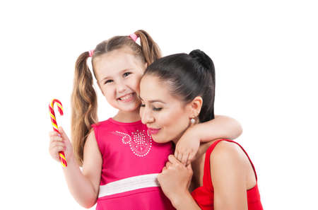 Happy loving family. mother and child girl playing, kissing and hugging. Laughing little girl in a red dress hugging her mother. Family values, relationships, human emotions.
