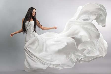흰 드레스를 비행에 아름 다운 어린 소녀입니다. 흐르는 직물. 바람에 날리는 밝은 흰색 천