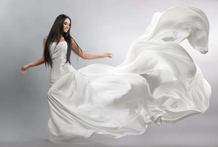 beautiful young girl in flying white dress. Flowing fabric. Light white cloth flying in the wind Imagens - 62374955