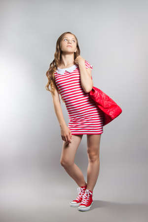 Pretty joyful little girl in a striped dress posing in the studio. Teenager with red bag. Stock Photo