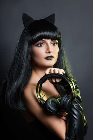 fashion beauty portrait of a beautiful young girl with headphones. Sexy woman in leather clothes with koshachmi ears on the hair.