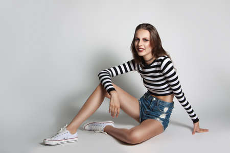 fashion photos: Pretty young girl in shorts and sweater striped posing in the studio. Beauty fashion photos. Model sitting on a gray background. Stock Photo