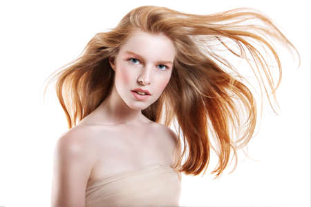 cream color: beautiful young woman with flying hair. Red hair flying in the wind. Stock Photo