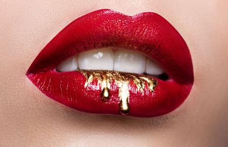 Mooie vrouwelijke lippenclose-up. Rode lippenstift, gouden verf die over zijn lippen stroomt. Stock Foto Cosmetisch adverteren