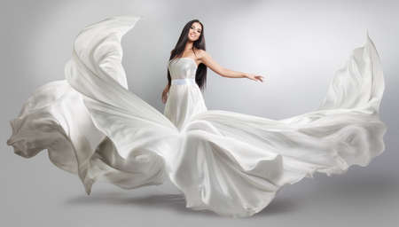 beautiful young girl in flying white dress. Flowing fabric. Light white cloth flying in the wind