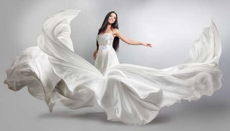 Piękne młoda dziewczyna w pływających pod białą sukienkę. Przepływająca tkanina. Jasno biała szmatka pływająca pod wiatr Zdjęcie Seryjne