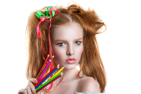 portrait of a beautiful young girl with colored pencils in hand. Girl with creative hairstyle and makeup holding pencils.