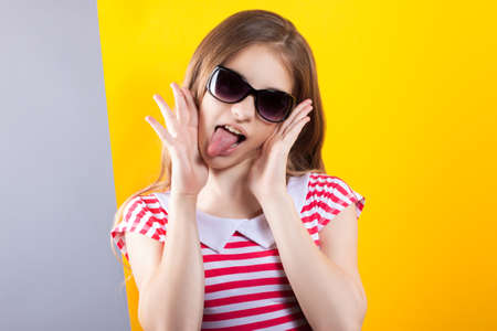 stock photos: pretty girl in sunglasses posing on a yellow-gray background. Bright stock photos. Positive human emotions