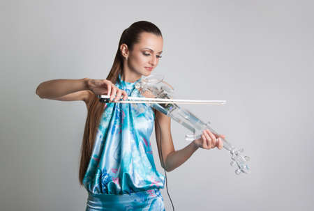 cute young violinist with a transparent electronic violin. Portrait of a girl with a violin on the gray background
