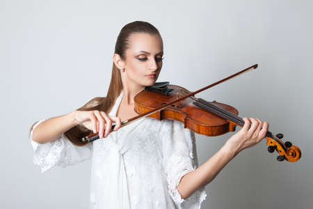 beautiful young woman playing the violin. Musician. Stock Photo Isolation on a gray background Stock Photo