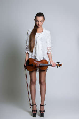beautiful young woman in a white dress with a violin in his hands. Classical music. Violin