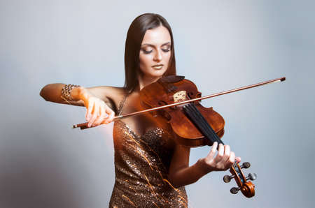 beautiful young woman in gold plays the violin. Musician. Classical music