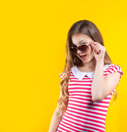 stock photos: pretty girl in sunglasses posing on a yellow background. Bright stock photos. Positive human emotions