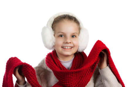 warm things: Joyful girl in warm winter things. The girl in fur ear-phones and a blouse with a red knitted scarf Stock Photo