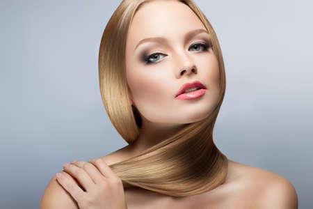 Beauty Woman Portrait. Parfait peau fraîche. santé cheveux bien coiffés. Jeunes et peau aux petits soins. Isolation sur gris