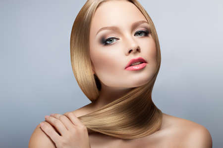 Beauty Woman Portrait. Perfect Fresh Skin. healthy well-groomed hair. Youth and Skin Care Concept. Isolation on gray