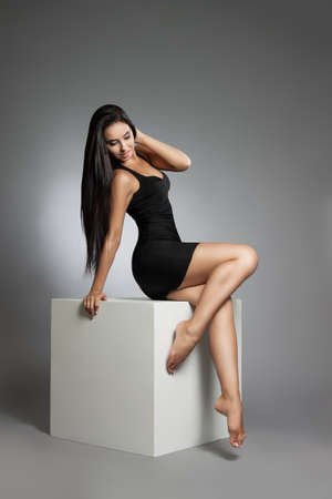 beauty fashion portrait of beautiful young girl in a black dress. Woman posing in the studio on a white cube