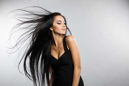 sleek: Beautiful girl model with flying the wind hair. A brunette woman in a black dress