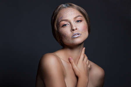 appearance: fashion beauty glamor girl. Face in Glitter Powder. Close-up portrait of a woman on a black background Stock Photo