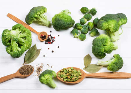 beautiful still life with herbs and spices on a wooden table. Horizontal top view. broccoli, brussels sprouts, bay leaf and spices for soup Stock Photo