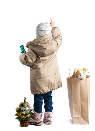 a little girl standing with his back pointing her finger. Girl in winter clothes on a white background. Stock Photo