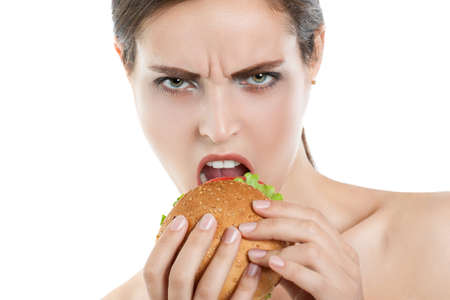 girl eating hamburger on white background. Close-up. dissatisfied face Stock Photo