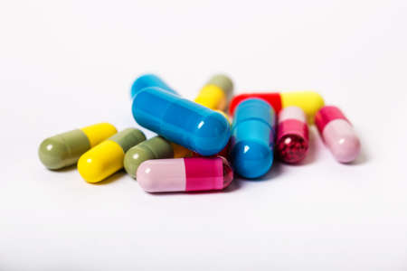 Assorted pharmaceutical medicine pills, multicolored tablets and capsules over white background