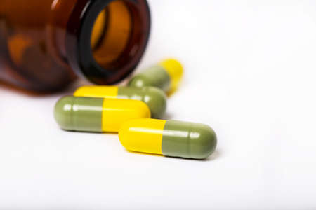 Colorful pills spilling out of a toppled bright red orange pill bottle. Yellow-green capsules on a white background Stock Photo