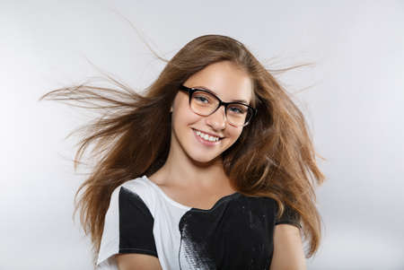 Smart beautiful girl with glasses. Flying in the wind hair. Beautiful smile Stock Photo