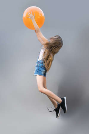 Joyful girl jumps holding an orange ball. Human emotions. flight. happiness. Stock Photo