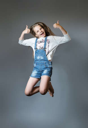 Lovely girl joyfully jumping. Cheerful teen girl in denim overalls on gray background