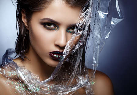 Beauty fashion model girl with bright make up. Fashion art portrait. With polyethylene film