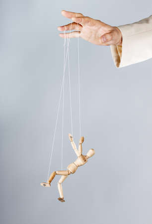 the figure of a wooden man tied ropes to the arm. Puppet. Man controls the action figures