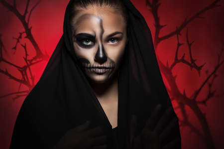 Halloween portrait of young beautiful girl in a black hood. skeleton makeup half face. Trees on a red background