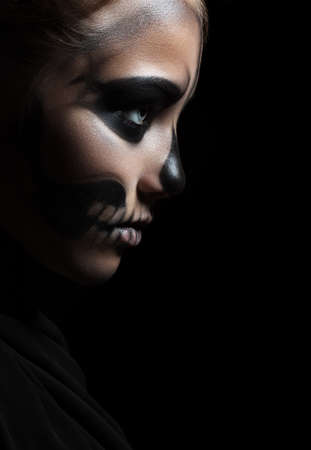 Closeup profile of a girl with make-up skeleton. Halloween portrait. Isolation on a black background