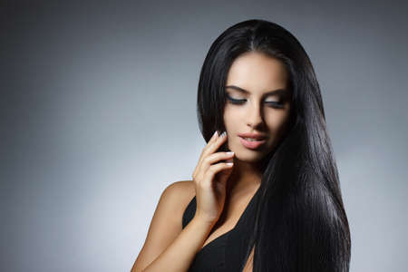 Beautiful model girl with smooth dark hair. Perfect hair. Black dress. Woman looking to the side Фото со стока