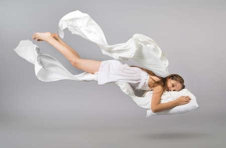 Śpiąca dziewczyna. Latanie we śnie. Biała pościel lecąca w powietrzu. Jasnoszare tło
