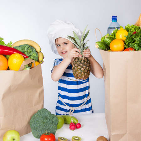 Little happy girl in chef hat with big bags of products. A variety of fresh fruits and vegetables in bags on the table. Healthy food. Child happy and healthy. Positive human emotion, facial expression feeling, attitude