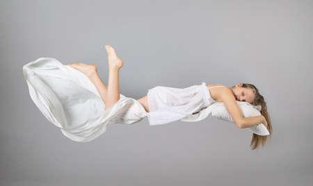 Slapend meisje. Vliegen in een droom. Wit linnen dat door de lucht vliegt. Lichtgrijze achtergrond