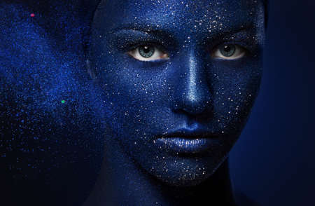beautiful girl face painted with blue paint with glitter. The effect of the destruction. flying powder particles 스톡 콘텐츠