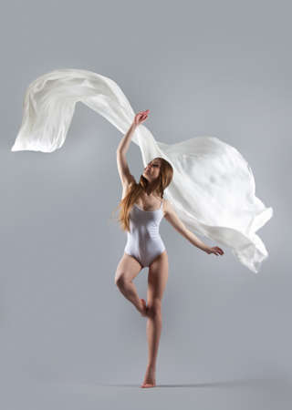 Young attractive girl dancing in the Studio with a white cloth. Fabric flies through the air. Model in white combidress