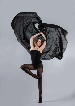 beautiful young girl dancing with black cloth. flying fabric. Gray background