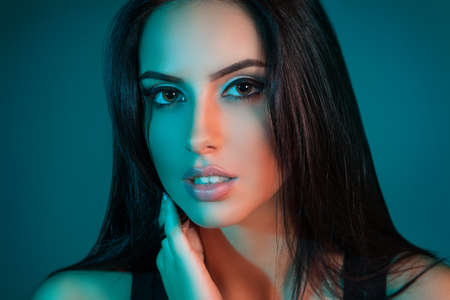 Creative Studio portrait of beautiful female model close-up. The blue lights. Looking at the camera
