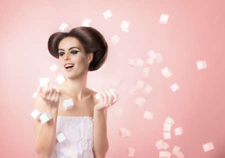 young beautiful model in a paper dress with voluminous cubes . creative makeup and hairstyle. pink background. Girl holding in hands white cubes Reklamní fotografie