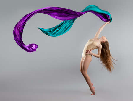 beautiful young girl dancing. Flowing fabric. The girl throws a colorful fabric. Fabric is flying. gray background Reklamní fotografie