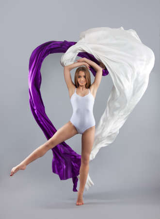 beautiful young girl dancing. Flowing fabric. A girl throws a white and purple cloth. Fabric is flying. gray background