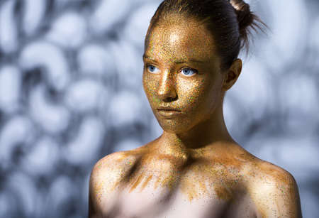 portrait of a beautiful young girl. Face painted with gold paint with glitter. abstract shadows on the background and on the model.