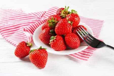 Fresh ripe strawberries on a plate. White wooden table, napkin in red and white stripes.