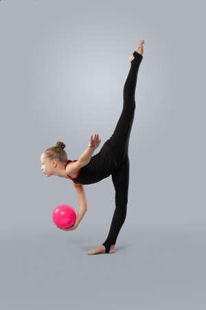 Belle gymnaste en tenue de sport avec ballon exécute un élément de gymnastique rythmique sur fond gris. La jambe est relevée haut.